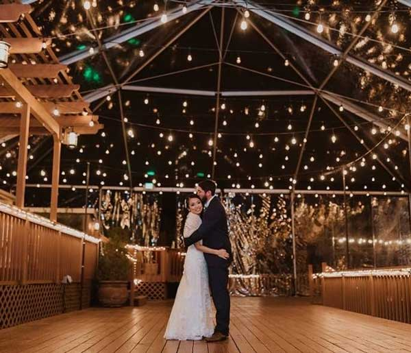 Bride and Groom dancing along on deck under lights at night