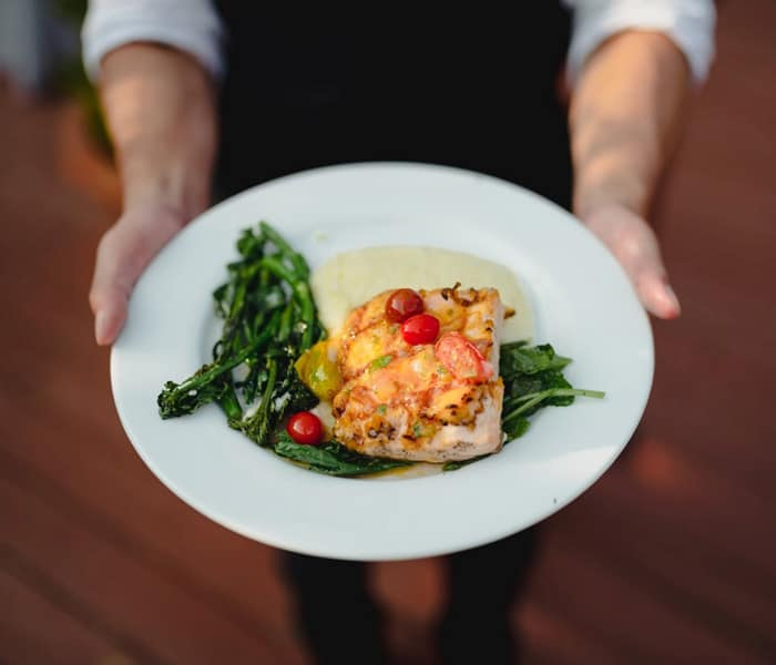 Salmon Dish Displayed in hands by Server
